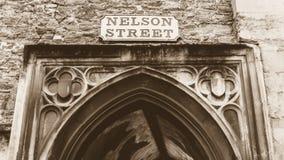 Nelson Street Old Name Signs ovanför valvgång i sepia Arkivbilder