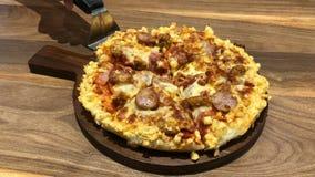 Nemend een stuk van vers gebakken eigengemaakte pizza volledige brij met het uitrekken van kaas op lijst stock video