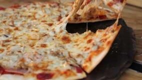 Nemend plak van eigengemaakte pizza met het uitrekken van kaas stock video