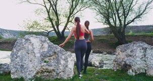 Nemend video van de rug in het midden van schitterend landschap van berg en rivier twee dames na een harde training stock video