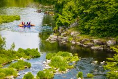 People kayaking along mountain river in spring. Extreme sport participants stock photography