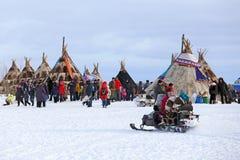 Nenets kvinnor går på en snövessla bland tält Arkivbild