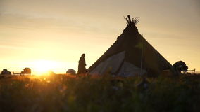Nenets woman walks into the chum at sunset. stock footage