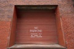 Nenhum estacionamento pintado em uma porta do armazém fotografia de stock