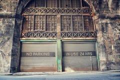 Nenhum lugar de estacionamento, no uso 24 horas de observação na garagem oxidada velha do ferro ondulado da pintura do vintage, E imagens de stock royalty free