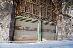 Nenhum lugar de estacionamento, no uso 24 horas de observação na garagem oxidada velha do ferro ondulado da pintura do vintage, E foto de stock