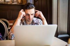 Nenhum minuto sem meu portátil Homem novo considerável que trabalha no portátil e no pensamento Imagens de Stock Royalty Free