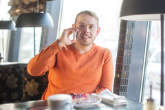 Nenhum minuto sem meu portátil Homem novo considerável que trabalha no portátil e que sorri ao apreciar o café no café Imagem de Stock
