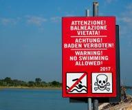 Nenhum sinal da natação com o ícone do crânio, escrito em três línguas Fotos de Stock Royalty Free