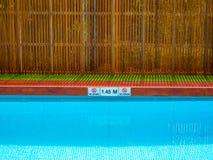 Nenhum sinal de mergulho e sinal da profundidade da associação na borda da associação na piscina exterior no fundo de madeira da  imagem de stock royalty free