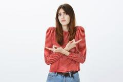 Nenhuma ideia aonde ir, menina da ajuda escolhe A mulher atrativa confusa nas listras reveste, cruzando as mãos e apontando dentr foto de stock