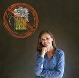 Nenhuma mão de sorriso da mulher do álcool da cerveja no queixo no fundo do quadro-negro foto de stock royalty free