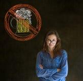 Nenhuma mulher do álcool da cerveja arma-se dobrado olhando o no fundo do quadro-negro imagens de stock