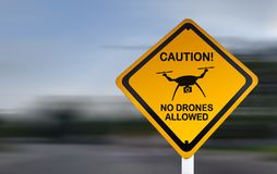 Nenhuns zangões permitidos - sinal amarelo do cuidado - a observação da limitação do espaço aéreo do voo fotografia de stock