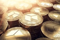 NEO coins in blurry closeup with sunburst from above. Royalty Free Stock Photo