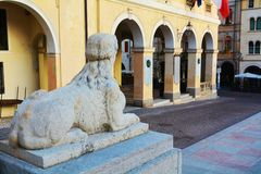 Neoclassic architecture in Conegliano Veneto, Treviso, Italy. Neoclassic architecture, sculptures, street, detail of a stone sphinx, and the Accademy Theatre, in Royalty Free Stock Photography