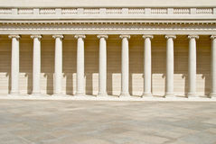 Neoclassical Columns. Row of Ionic columns and plaza in neoclassical building warm sunshine stock photography