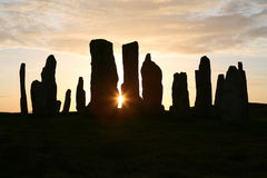 Neolithic Sunset. Sun setting behind the neolithic stone circle at Callanish, Isle of Lewis, Outer Hebrides Royalty Free Stock Images