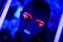 Neon art make up. Woman face with fluorescent make up art. Blue background. Studio shot. Orange, pink, blue neon paints. Creative idea is good for clubs, disco Royalty Free Stock Photography