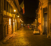 Neon beleuchtete Kopfsteinstraße, Rom, Italien Stockbilder