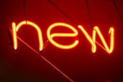 Neon beschriftet NEUES Zeichen, Dekoration Art Anzeige zu beleuchten Lizenzfreie Stockfotos