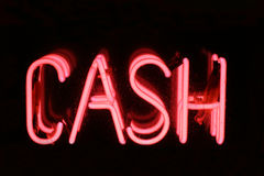 Neon Cash Sign. A Pink neon sign spelling out the words CASH. Set on a black background Royalty Free Stock Photo