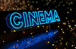 Neon Cinema Sign. On dark blurred background Stock Photography