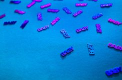 Neon colored confetti baby on blue background. Neon colored confetti with words baby scattered on blue background with copy space. Modern trendy baby shower royalty free stock photography