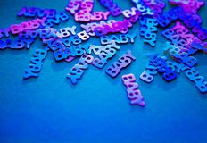 Neon colored confetti baby on blue background. Neon colored confetti with words baby scattered on blue background with copy space. Modern trendy baby shower stock photo