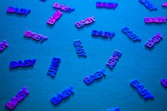 Neon colored confetti baby on blue background. Neon colored confetti with words baby scattered on blue background. Modern trendy baby shower template for royalty free stock photography