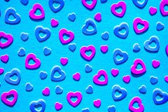 Neon colored heart confetti on blue background. Neon colored heart confetti scattered on blue background. Modern trendy flat lay design background for royalty free stock photography