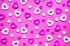 Neon colored heart confetti on pink background. Neon colored heart confetti scattered on pink background. Modern trendy flat lay design background for stock photography