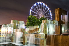 Seattle Great Wheel and Modern Fountain Sculpture at Night. Vibrant Lights Illuminate Modern Fountain Sculpture in Night Scene with Seattle Great Wheel in Stock Photo
