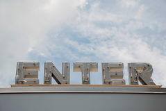 Neon Enter Sign. An unlit neon sign welcoming visitors. The word enter is in a capital letters and is framed by a bright blue sky Stock Photos
