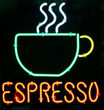 Neon espresso. Neon sign spelling espresso and with a steaming cup of coffee Stock Photos