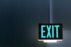 Neon exit sign. Lit exit sign hanging from the ceiling Stock Photo