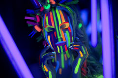 Neon face art. Woman's face with fluorescent make up art. Blue background. Studio shot. Orange, green, yellow neon paints. Creative idea is good for clubs, disco Royalty Free Stock Images
