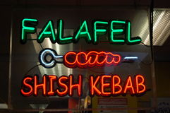 Neon falafel and shish kebab. A neon sign in a restaurant window advertises falafel and shish kebab Stock Image