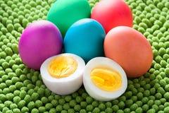 Neon farbiges Ostereistillleben mit offenem hart gesotten Ei des Schnittes lizenzfreie stockbilder