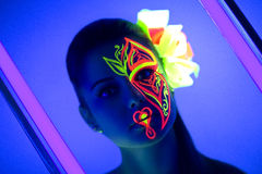 Neon flower make up. Woman's face with fluorescent make up art. Blue background. Studio shot. Orange, green, pink neon paints. Creative idea is good for clubs Royalty Free Stock Image