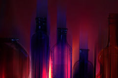 Neon Glass Bottles. Antique glass bottles with neon light effects from multiple exposures royalty free stock images