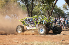 Neon green car kicking up dust during speed timed trial event Royalty Free Stock Image