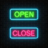 Neon green open and red close glowing signs in geometric shape on a brick wall background. Royalty Free Stock Image