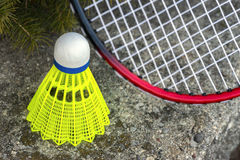 Neon green shuttlecock and red badminton racket leaning on stone. Wall, closeup, recreational activity background Stock Images
