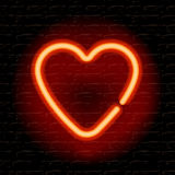 Neon heart on the brick wall Stock Photos