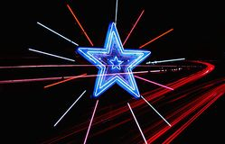 Neon Highway Star. Graphic neon star with streaking tail lights passing by on the Highway Stock Photo