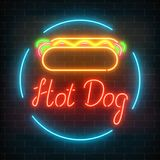 Neon hot dog cafe glowing signboard on a dark brick wall background. Fastfood light billboard sign. Royalty Free Stock Photography
