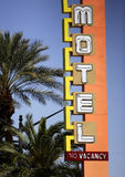 Neon Hotel/Casino Sign. Bright and blinking neon lights advertising a hotel/casino in downtown Las Vegas are shown at daytime. Palm trees nearby Royalty Free Stock Photos