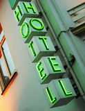 Neon hotel sign. Green neon hotel sign in evening light with hotel window Royalty Free Stock Photos