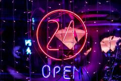 Neon 24 hours open logo sign glowing in the bar store f stock photo
